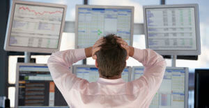 Stock Trader Watching Computer Screens With Hands On Head