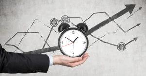 businessman's hand holds an alarm clock.